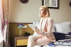 Businesswoman sitting on bed and using tablet. Portrait of beautiful businesswoman sitting on bed and using digital tablet. Woman working in hotel room. Business Royalty Free Stock Photo