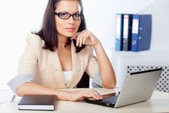 Businesswoman sitting behind the desk Stock Photography