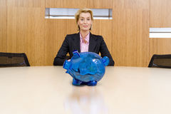Businesswoman sitting behind piggy bank royalty free stock images