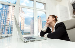 Businesswoman sitting behind table and looking out of window Stock Photos