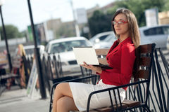 Businesswoman  sitting on bench looking at camera Royalty Free Stock Photos