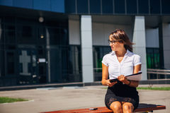 Businesswoman sitting on a bench at lunchtime and talking the phone Royalty Free Stock Photos