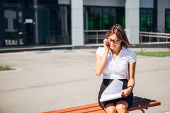 Businesswoman sitting on a bench at lunchtime and talking  the phone Royalty Free Stock Image