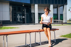 Businesswoman sitting on a bench at lunchtime and talking the phone Stock Photography