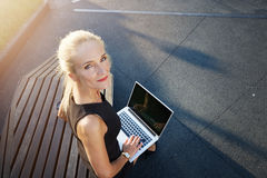 Businesswoman sitting on bench working outside Stock Photography