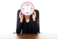 Businesswoman sitting with big clock at the office Stock Image