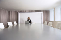 Businesswoman Sitting In Boardroom With Laptop Royalty Free Stock Images