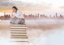 Businesswoman sitting on Books stacked by distant city Stock Images