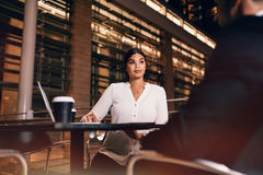 Businesswoman sitting at cafe in airport table with businessman. Young businesswoman sitting at cafe table with businessman. Business people waiting at airport Stock Photo