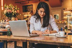 Businesswoman is sitting in cafe at table in front of laptop, making notes in notebook, working.Student learning online. Young businesswoman is sitting in cafe Royalty Free Stock Image