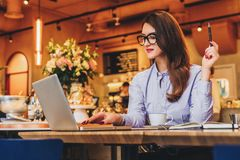 Businesswoman is sitting in cafe at table, working on laptop. Hipster girl blogging, browsing internet, checking email. Stock Image