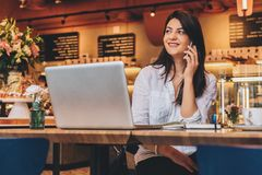 Businesswoman is sitting in cafe at wooden table in front of laptop and talking on cell phone. Telephone conversations. Young businesswoman dressed in white royalty free stock image