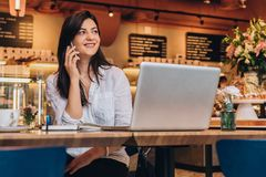 Businesswoman is sitting in cafe at wooden table in front of laptop and talking on cell phone. Telephone conversations. Young businesswoman dressed in white royalty free stock images