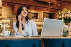 Businesswoman is sitting in cafe at wooden table in front of laptop and talking on cell phone. Telephone conversations. Young businesswoman dressed in white stock images