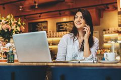 Businesswoman is sitting in cafe at wooden table in front of laptop and talking on cell phone. Telephone conversations. Young businesswoman dressed in white stock photos