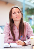 Businesswoman sitting in a cafe and writing in notepad or organi Stock Photos