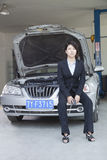 Businesswoman Sitting on Car With Open Hood Royalty Free Stock Photography