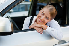 Businesswoman sitting in the car and smiling Royalty Free Stock Photography