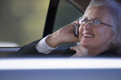 Businesswoman sitting in car, using mobile phone, view through window, smiling, side view Stock Image