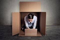 Businesswoman sitting in carton box working on laptop computer. Closeup young businesswoman hiding sitting in the carton box working on laptop computer Stock Images