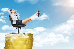 Businesswoman sitting in chair on coins stack Royalty Free Stock Photo