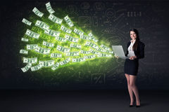 Businesswoman sitting in chair holding laptop with dollar bills Stock Photo