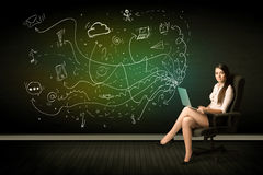 Businesswoman sitting in chair holding laptop with media icons Royalty Free Stock Photo