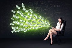 Businesswoman sitting in chair holding tablet with dollar bills Stock Photos