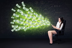 Businesswoman sitting in chair holding tablet with dollar bills Royalty Free Stock Images