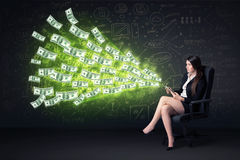 Businesswoman sitting in chair holding tablet with dollar bills Royalty Free Stock Photos