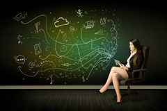 Businesswoman sitting in chair holding tablet with media icons Royalty Free Stock Images