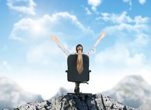 Businesswoman sitting in chair on mountain top Stock Images