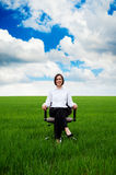 Businesswoman sitting on chair over green field Royalty Free Stock Image