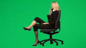 Businesswoman sitting on a chair on phone against green screen footage