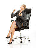 Businesswoman sitting on a chair and pointing Stock Photos