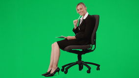 Businesswoman sitting on a chair writing notes against green screen