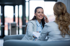 Businesswoman sitting with colleague and talking on mobile phone Stock Image