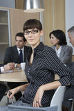 Businesswoman Sitting With Colleagues Working In Background Royalty Free Stock Photo