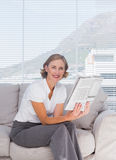 Businesswoman sitting on couch and holding newspaper Royalty Free Stock Image
