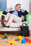 Businesswoman sitting on couch at messy room Stock Images