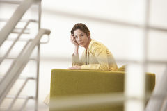 Businesswoman Sitting On Couch In Office. Portrait of relaxed young businesswoman sitting on couch in office Stock Photography