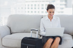 Businesswoman sitting on the couch using laptop Stock Image
