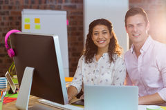 Businesswoman sitting with coworker while working on computer Royalty Free Stock Image