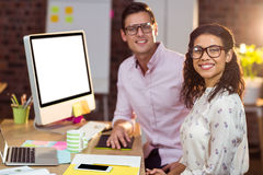 Businesswoman sitting with coworker while working on computer Royalty Free Stock Photo