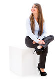 Businesswoman sitting on a cube. Royalty Free Stock Image
