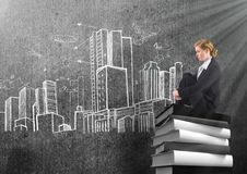 Businesswoman sitting on 3D Books stacked by city buildings drawings Stock Photo