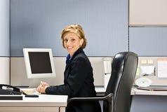Businesswoman sitting at desk Stock Photo