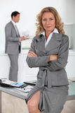 Businesswoman sitting on desk Stock Photos