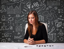 Businesswoman sitting at desk with business scheme and icons Stock Photos