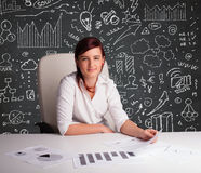 Businesswoman sitting at desk with business scheme and icons Royalty Free Stock Photography